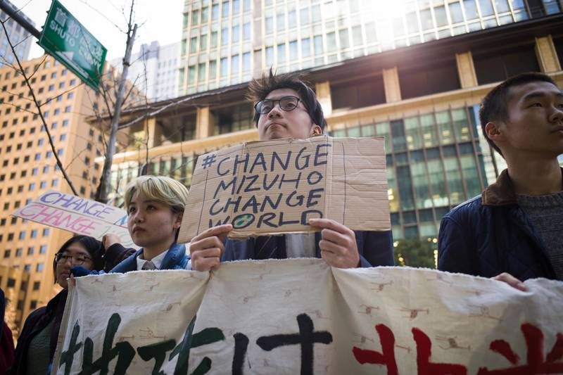 A group of youth climate activists hold up a protest banner and placards outside the Mizuho Financial Group Inc. headquarters in Tokyo, Japan, on Friday, March 6, 2020. The anti-coal demonstration organized by Fridays for Future Tokyo denounced Mizuho Bank's role in financing coal projects globally. Photographer: Kentaro Takahashi/Bloomberg