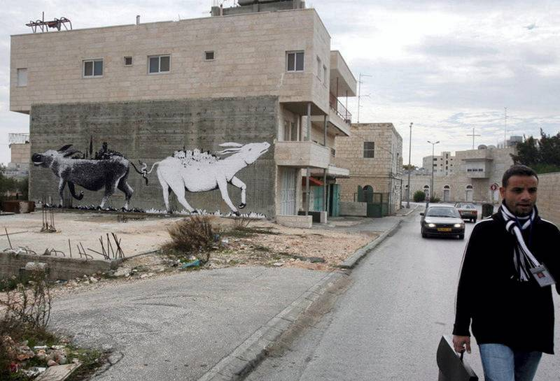 epa01191069 Illusive British graffiti artist named Banksy has painted new works in the West Bank town of Bethlehem, which might include a huge painting of two donkeys with their tails entwined pulling each other, as seen on the side of a house in Bethlehem as a Palestinian walks past on 04 December 2007. The white donkey has what appears to be a pastoral palestinian village on its back and the black donket carries on its back what appears to be a modern Israeli town or cityscape. Banksy's works are not signed.  EPA/JIM HOLLANDER *** Local Caption *** 01191069