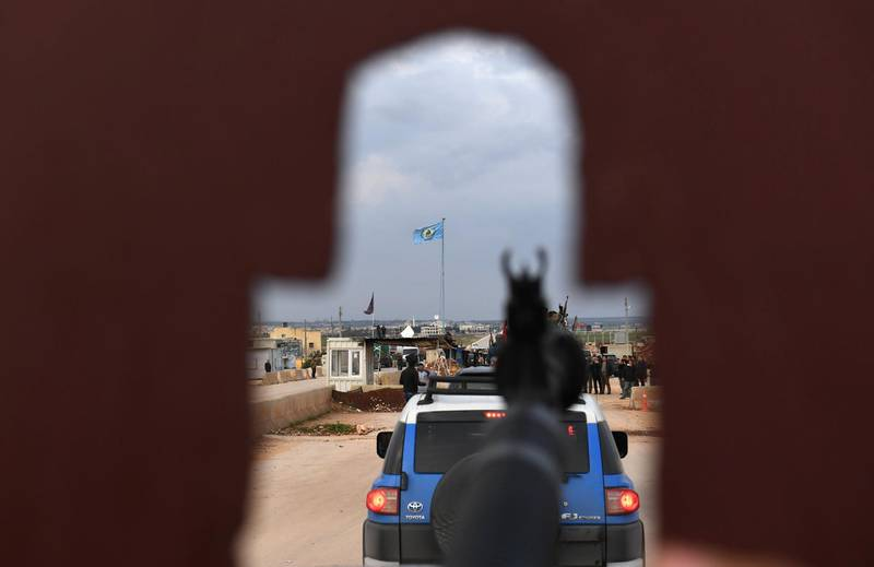"""A picture taken on February 20, 2018 through the turret of a gun mounted on a vehicle shows a convoy of pro-Syrian government fighters arriving in Syria's northern city of Afrin. Kurdish forces said in a statement on February 20 that pro-regime fighters deployed to Syria's Afrin region will take up positions and """"participate in defending the territorial unity of Syria and its borders"""", countering Turkey's offensive on the area. / AFP PHOTO / George OURFALIAN"""