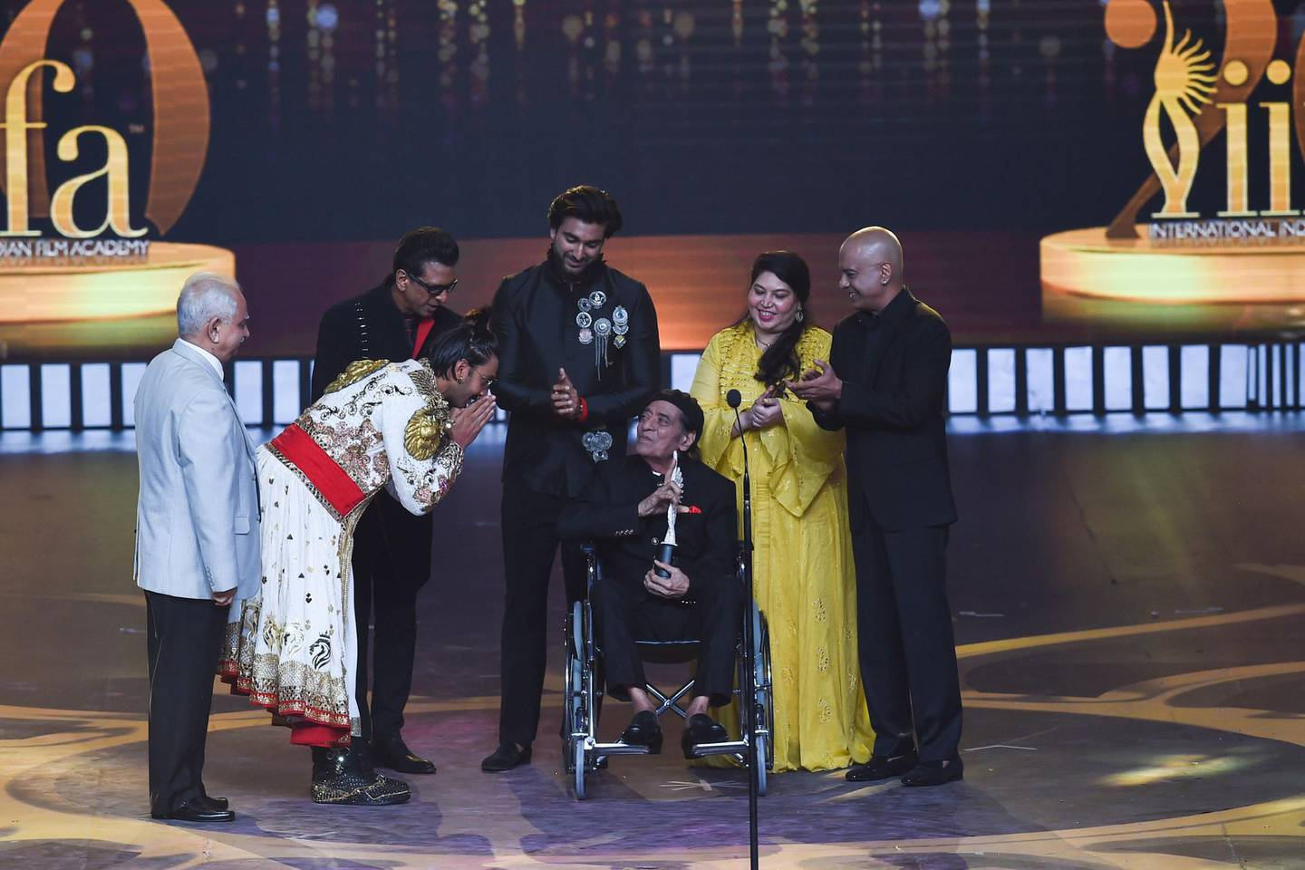 Bollywood actor Ranveer Singh (2L) bows after actor Jagdeep (C) received the Lifetime Achievement award during the 20th International Indian Film Academy (IIFA) Awards at NSCI Dome in Mumbai early on September 19, 2019. / AFP / INDRANIL MUKHERJEE