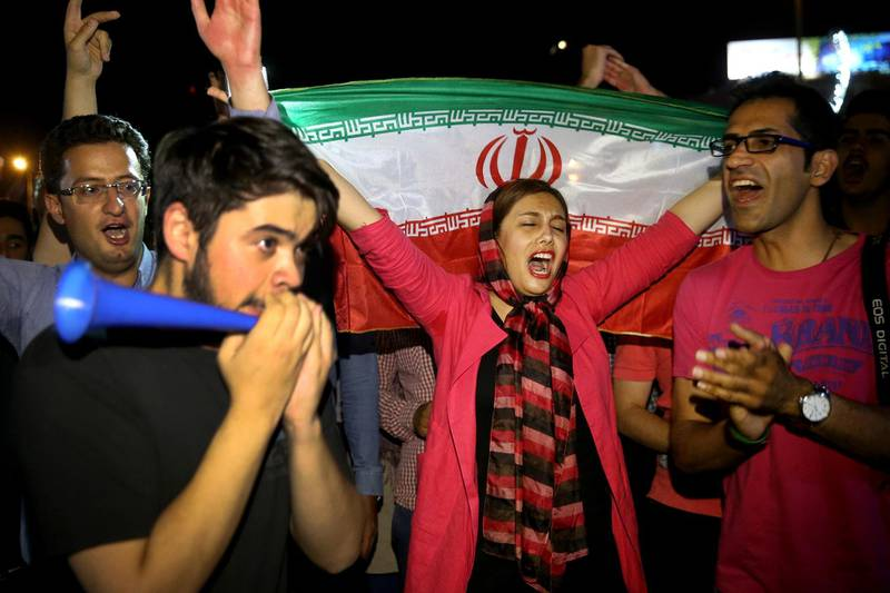 """FILE - In this July 14, 2015 file photo, an Iranian woman holds up a national flag as people celebrate a landmark nuclear deal, in Tehran, Iran. The race for the White House could mean another four years of President Donald Trump's """"maximum pressure"""" campaign of crippling sanctions. Or it could bring Joe Biden, who has raised the possibility of the U.S. returning to Iran's 2015 nuclear deal with world powers. (AP Photo/Ebrahim Noroozi, File)"""