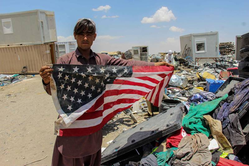 epa09227140 An Afghan man shows a US flag as he visits a junk yard to buy items which were discarded by the US and NATO forces, at a yard in Kandahar, southern Afghanistan, 25 May 2021. As the US and NATO forces withdraw, they destroyed most of the equipment under their use leaving behind decades of war, selling the scrap for millions of dollars to those willing to buy it.  EPA/M. SADIQ