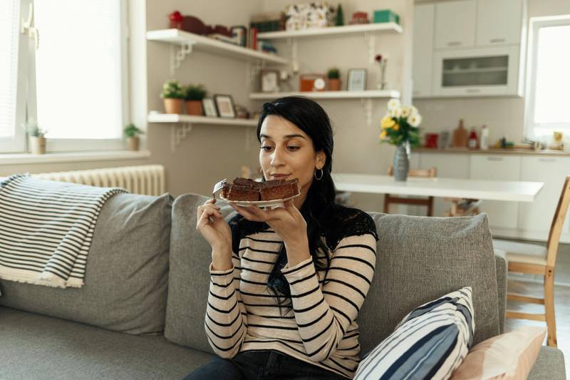 Young Woman Eating Unhealthy Food. Sweetness Indulging and Fattening Concept. Girl Biting Chocolate Cake, High-calorie Sweet Food, Increased Glucose Diabetes. Sweet food addiction.