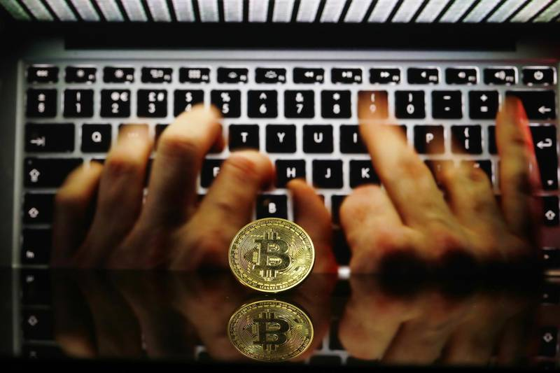 A coin representing Bitcoin cryptocurrency sits reflected on a polished surface and photographed against a backdrop image of hands entering data into a laptop computer in this arranged photograph in London, U.K., on Thursday, Feb. 8, 2018. Cryptocurrencies tracked by Coinmarketcap.com have lost more than $500 billion of market value since early January as governments clamped down, credit-card issuers halted purchases and investors grew increasingly concerned that last year's meteoric rise in digital assets was unjustified. Photographer: Luke MacGregor/Bloomberg /Bloomberg
