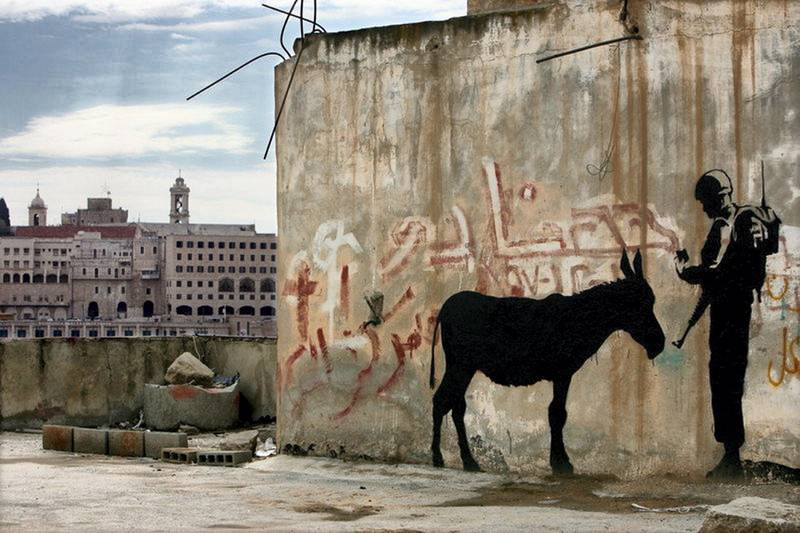epa01191023 Illusive British graffiti artist named Banksy has painted new works in the West Bank town of Bethlehem including  this stenciled work showing an Israeli soldier asking a donkey for it's identity card, on 04 December 2006. Behind, at left, is the old town of Bethlehem, with towers from the Church of the Nativity, the traditional birthplace of Jesus Christ. These new works are being dubbed 'West Banksy,' and some are painted on the controversial Israeli 'separation barrier,' or wall, that surrounds Bethlehem and cuts its residents off from nearby Jerusalem.  EPA/JIM HOLLANDER *** Local Caption *** 01191023
