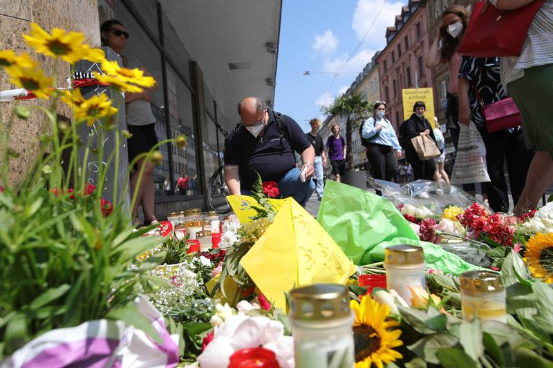 People place flowers and candles at a makeshift memorial in tribute to the victims of a deadly attack in the city center of Wuerzburg, southern Germany, on June 26, 2021. Investigators were racing to pinpoint the motive of a man who went on a knife rampage in the German city of Wuerzburg, killing three people and leaving five seriously injured. The suspect, a 24-year-old Somali who arrived in Wuerzburg in 2015, staged the attack in the city centre on the evening of Friday, June 25, 2021, striking at a household goods store before advancing to a bank. / AFP / ARMANDO BABANI