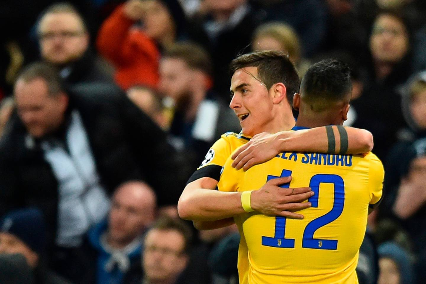 Juventus' Argentinian striker Paulo Dybala celebrates with Juventus' Brazilian defender Alex Sandro (R) after scoring their second goal during the UEFA Champions League round of sixteen second leg football match between Tottenham Hotspur and Juventus at Wembley Stadium in London, on March 7, 2018. / AFP PHOTO / Glyn KIRK