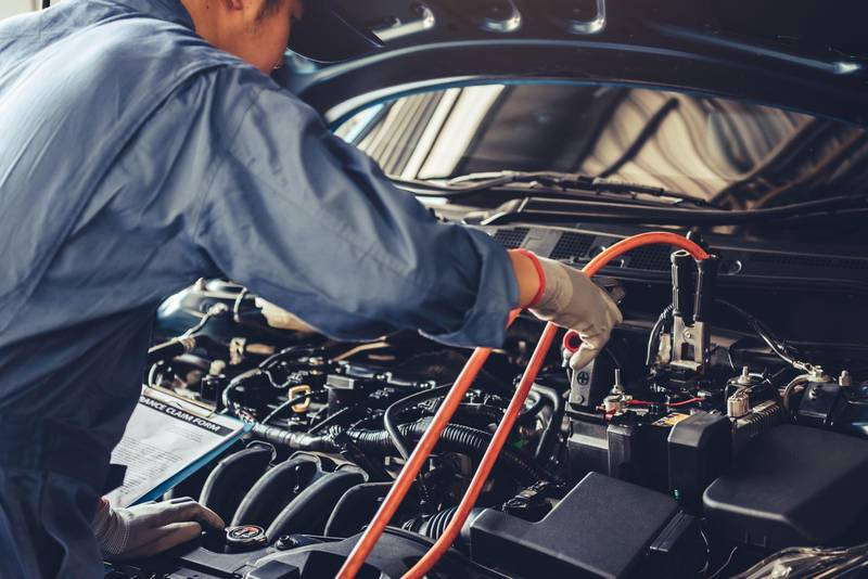 2BJ7JC0 Car mechanic holding battery electricity trough cables jumper and checking to maintenance vehicle by customer claim order in auto repair shop garage. Alamy