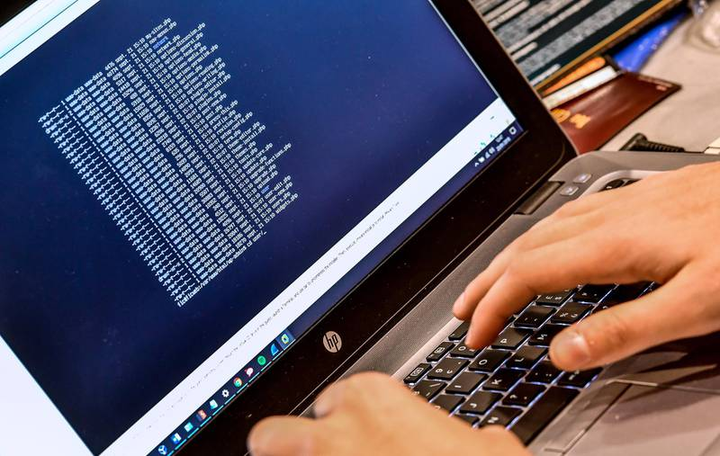 """(FILES) In this file photo taken on January 23, 2018 a person works at a computer during the 10th International Cybersecurity Forum in Lille, France.  The threat of cyberattacks against the US is at a """"critical point,"""" the country's intelligence chief has warned, branding Russia the most """"aggressive foreign actor"""" ahead of President Donald Trump's meeting with Vladimir Putin. / AFP PHOTO / PHILIPPE HUGUEN"""