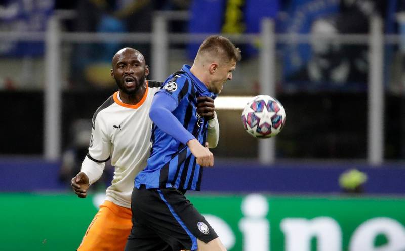 Atalanta's Josip Ilicic, front, duels for the ball with Valencia's Eliaquim Mangala during the Champions League round of 16, first leg, soccer match between Atalanta and Valencia at the San Siro stadium in Milan, Italy, Wednesday, Feb. 19, 2020. (AP Photo/Luca Bruno)