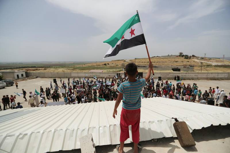 A boy holds the Free Syrian army flag during a protest calling for an end to the strikes and for Ankara to open the frontier at the Atmeh crossing on the Syrian-Turkish border, in Idlib governorate, Syria May 31, 2019. REUTERS/Khalil Ashawi