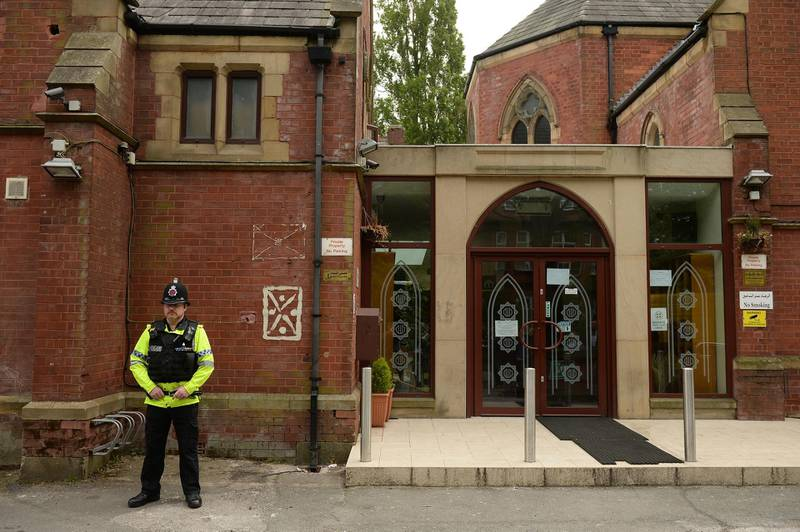 Police officers stand on duty outside a Didsbury Mosque in Didsbury, Manchester, northwest England, on May 24, 2017, as investigations continue into the May 22 terror attack at the Manchester Arena. Police on Tuesday named Salman Abedi -- reportedly British-born of Libyan descent -- as the suspect behind a suicide bombing that ripped into young fans at an Ariana Grande concert at the Manchester Arena, as the Islamic State group claimed responsibility for the carnage. Abedi's family are said to heve been closely linked to the Didsbury Mosque, a Victorian former Methodist chapel in a leafy suburb that was bought in 1967 by donors from the Syrian community. / AFP PHOTO / Oli SCARFF
