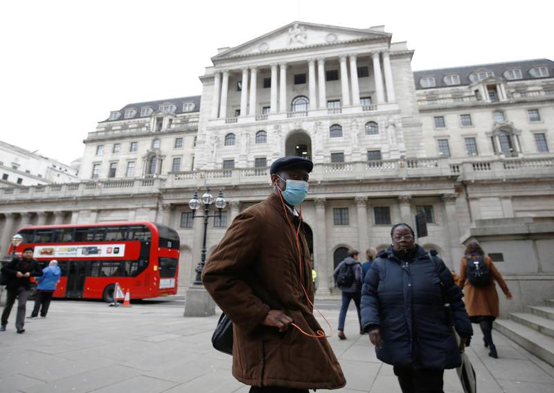 FILE PHOTO: A man, wearing a protective face mask, walks in front of the Bank of England, following an outbreak of the coronavirus, in London, Britain March 11, 2020. REUTERS/Henry Nicholls/File Photo