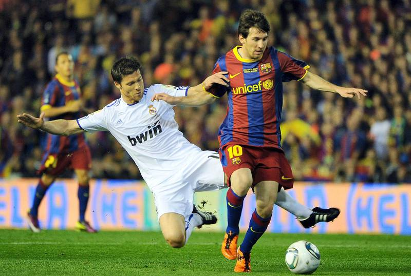 Real Madrid's midfielder Xabi Alonso (L) vies for the ball with Barcelona's Argentinian forward Lionel Messi (R)  during the Spanish Cup final match Real Madrid against Barcelona at the Mestalla stadium in Valencia on April 20, 2011.AFP PHOTO/ JOSE JORDAN (Photo by JOSE JORDAN / AFP)