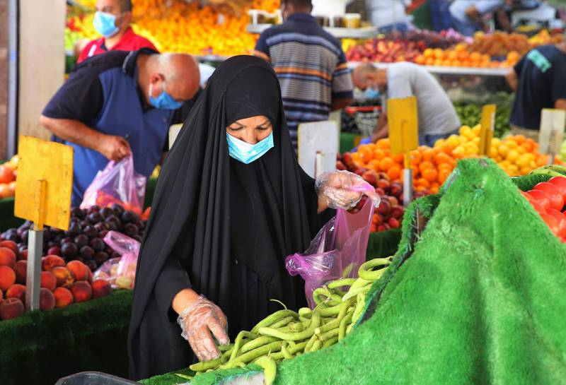 An Iraqi woman wearing a protective mask amid the COVID-19 pandemic, buys fresh produce from a street seller at a market in Karrada, in the capital Baghdad, on July 14, 2020. Iraq, in a bid to prevent the spread of the deadly COVID-19 illness, shut its 32 border crossings to goods and people coming from Iran, Turkey, Syria, Jordan and Saudi Arabia in mid-March, which helped its agriculture ministry accelerate a campaign to make Iraqi food markets self-sustainable, after years of relying on foreign imports for half of their supply. / AFP / AHMAD AL-RUBAYE