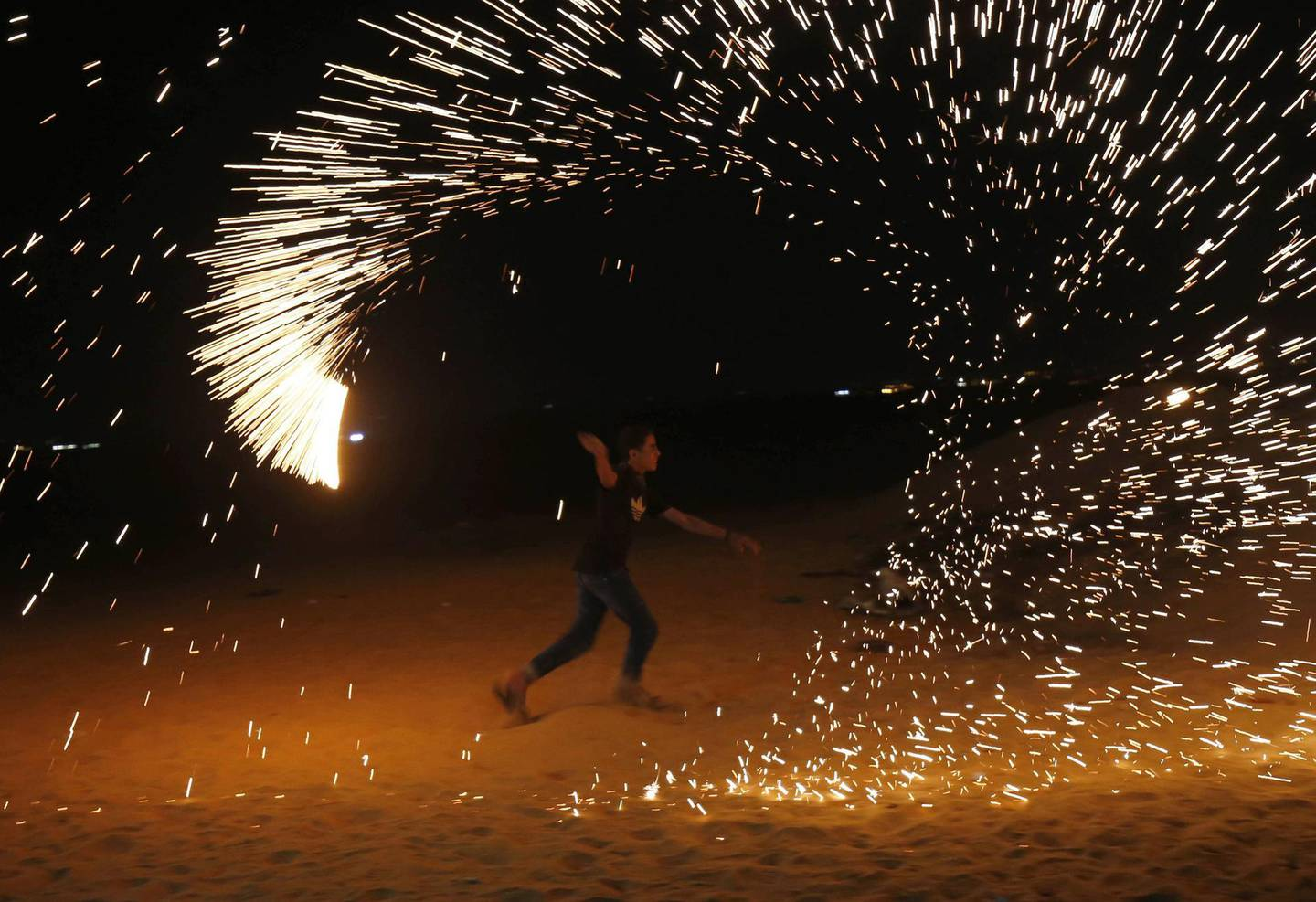 """A Palestinian protester from a group calling themselves the """"night confusion units"""" waves a sparkler near the Gaza-Israel border east of Rafah in the southern Gaza Strip, on September 26, 2018. The border protests since March 30 have been labelled the """"Great March of Return"""" because they call for Palestinian refugees to return to their former homes inside what is now Israel. Hundreds of thousands of dollars in damage were caused to Israeli land -- including incinerated crops -- by the kites and balloons, Israeli authorities said. / AFP / SAID KHATIB"""