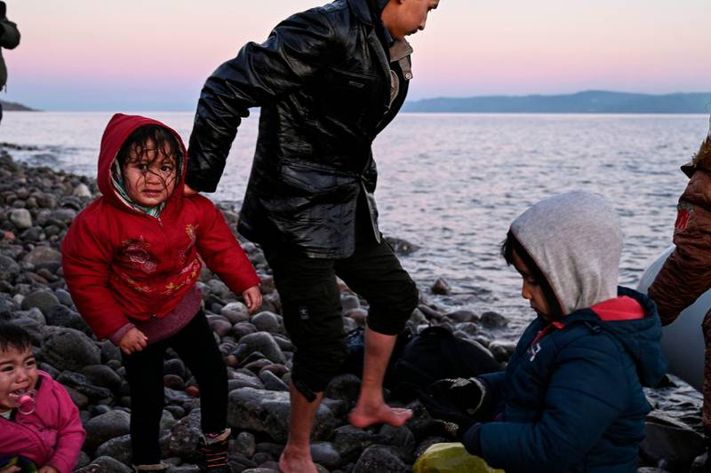 TOPSHOT - Refugees and migrants land ashore the Greek island of Lesbos on March 2, 2020. Around 500 migrants landed on Sunday morning in around 10 vessels, according to an AFP tally, their crossing made easier by the good weather conditions. Another four vessels carrying 120 people landed on the neighbouring island of Chios, and two vessels carrying 80 migrants landed on Samos, further to the south, ANA reported. According to the Greek coastguard, around 180 migrants arrived Saturday on Lesbos and Samos, making the crossing from Turkey despite strong winds.  / AFP / ARIS MESSINIS