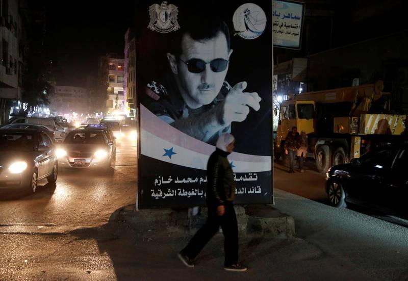 A woman walks past a poster depicting Syria's President Bashar al-Assad in Damascus, Syria March 5, 2020. REUTERS/Yamam Al Shaar