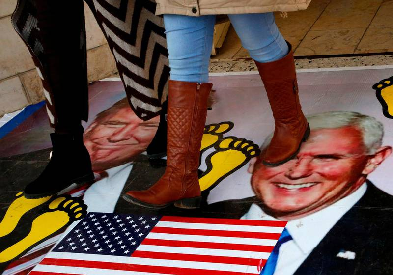 Palestinians walk on a poster bearing images of US President Donald Trump (L) and his deputy Mike Pence during a demonstration at the al-Quds Open University in Dura village on the outskirts of the West Bank town of Hebron on December 13, 2017, as protests continue in the region amid anger over US President Donald Trump's recognition of Jerusalem as its capital.  / AFP PHOTO / HAZEM BADER