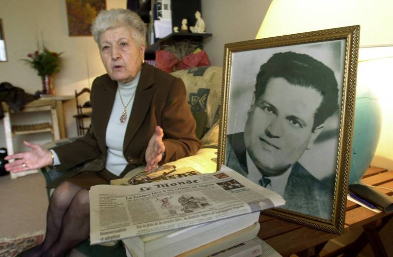 """(FILES) In this file photo taken on May 5, 2001 Malika Boumendjel, widow of Algerian lawyer Ali Boumendjel gives an intervie at her home in Puteaux, on her husband's death during his 43 days detention by the French army on March 23, 1957. French President Emanuel Macron admits on March 2, 2021 that underground resistance Algerian Liberation Front (FLN) lawyer Ali Boumendjel was """"tortured and murdered"""" by the French army during the war in Algeria. / AFP / Eric Feferberg"""