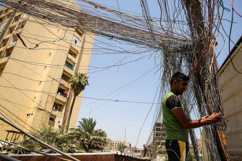 A man checks the wiring on electric cables reaching out to homes in Saadoun Street in the Iraqi capital Baghdad on July 29, 2018, as chronic power shortages have forced residents to buy electricity from private entrepreneurs who run generators on street corners across the country. - Iraqi Prime Minister Haider al-Abadi sacked his minister of electricity on July 29 after three weeks of protests against corruption and chronic power cuts in the energy-rich country where successive conflicts have devastated infrastructure. (Photo by SABAH ARAR / AFP)