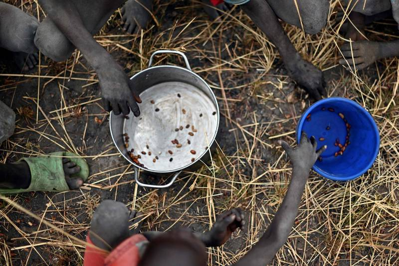 (FILES) In this file photo taken on February 6, 2020 children collect grain spilt on the field from gunny bags that ruptured upon ground impact following a food drop from a plane at a village in Ayod county, South Sudan, where World Food Programme (WFP) have just carried out a food drop of grain and supplementary aid. The UN appealed on December 1, 2020  for a record $35 billion to provide aid in 2021, as the pandemic left tens of millions more people in crisis, and with the risk of multiple famines looming. The world body's annual Global Humanitarian Overview estimated that 235 million people worldwide will need some form of emergency assistance next year -- a staggering 40-percent increase in the past year.  / AFP / TONY KARUMBA