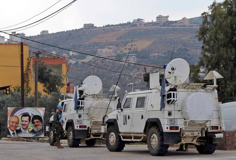 """United Nations Interim Forces in Lebanon (UNIFIL) vehicles and armoured personnel carriers (APC) are seen on a road near the border between the southern Lebanese village of Kfar Kila and Israel on December 4, 2018, with a poster depicting Lebanese parliament speaker Nabih Berri (L), Syrian President Bashar al-Assad (C), and Hezbollah leader Hasan Nasrallah (R) seen in the corner. Israel's army said on December 4 it had detected Hezbollah """"attack tunnels"""" infiltrating its territory from Lebanon and had launched an operation called """"Northern Shield"""" to destroy them, a move likely to raise tensions with the Iran-backed group. / AFP / Ali DIA"""
