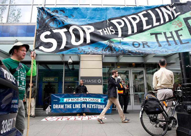 (FILES) In this file photo Indigenous leaders and climate activists disrupt business at a Chase Bank branch in Seattle  on May 8, 2017.  President-elect Joe Biden plans to scrap the permit for the controversial Keystone XL oil pipeline between Canada and the US, two Canadian broadcasters said on January 17, 2021. CBC and CTV cited sources and notes from Biden's transition team that indicate he will rescind the permit via executive order following his inauguration on January 20, 2021.  / AFP / Jason Redmond