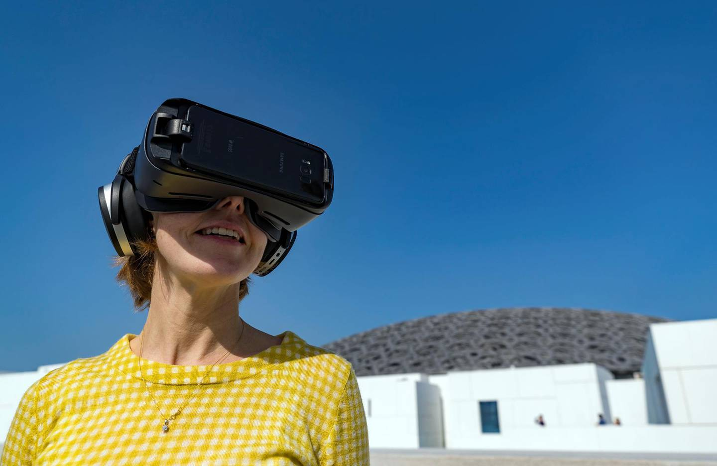 Abu Dhabi, United Arab Emirates - February 15th 2018: Reporter Melissa Gronlund trying on the VR headset at a press conference about the Highway Gallery located along the E11. Thursday, February 15th, 2018. The Louvre, Abu Dhabi. Chris Whiteoak / The National