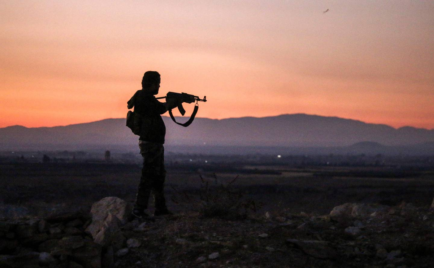 TOPSHOT - A Syrian rebel fighter aims his Kalashnikov assault rifle as he stands near the frontline against government forces west of the embattled southern city of Daraa on July 3, 2018.  / AFP / Mohamad ABAZEED