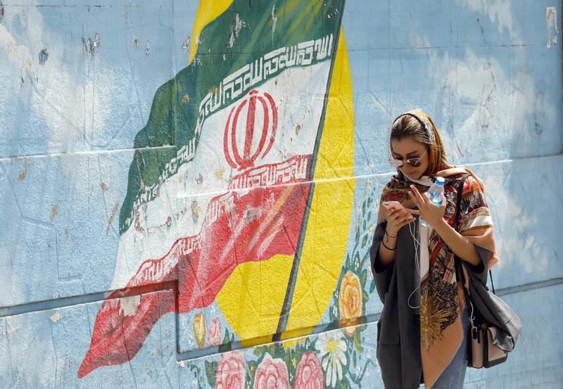 epa06698529 An Iranian girl walks next to a wall painting of Iran's national flag while using her cellphone in a street, in Tehran, Iran, 28 April 2018. Iranian government officially lunched home-made app 'Soroush' with list of emojis in the form of little veiled women with special political messages. The new app was released to replace the popular messaging service Telegram, which was reportedly banned in the county after it was extensively used in communications during the 2017 anti-government protests.  EPA/ABEDIN TAHERKENAREH