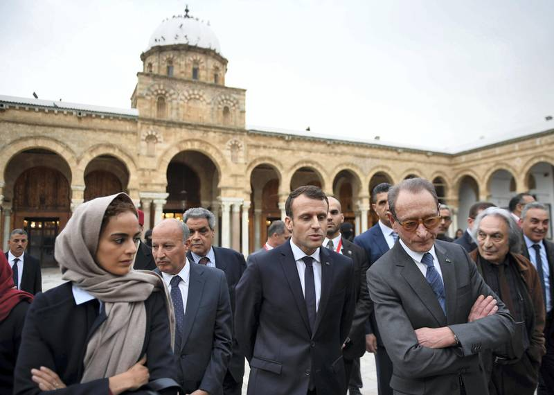 French President Emmanuel Macron (C) stands with Paris' former mayor Bertrand Delanoe (C-R) in the courtyard of the Zitouna mosque in the Medina (old town) of the Tunisian capital Tunis on February 1, 2018, during Macron's first state visit to the North African country. / AFP PHOTO / POOL / Eric FEFERBERG