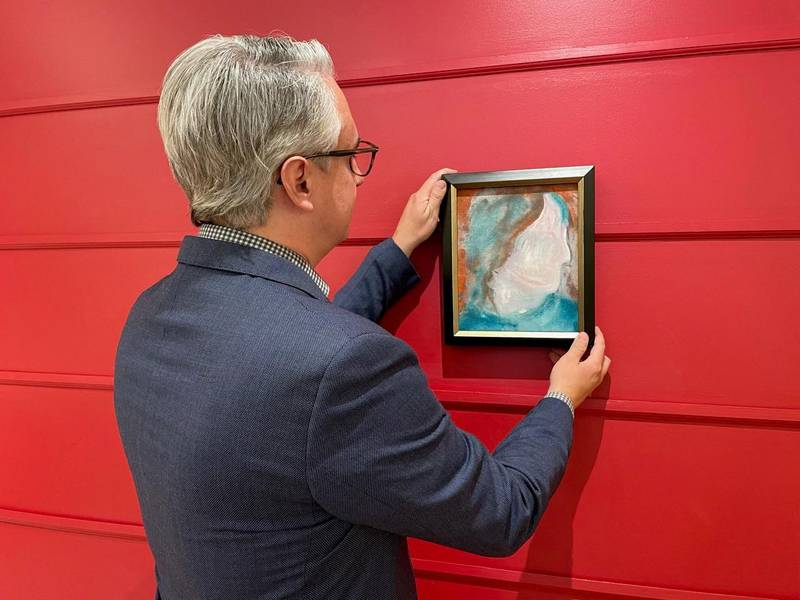 """A handout photo released on June 15, 2021, courtesy of the auction house Cowley Abbott shows Canadian Art Specialist Rob Cowley with a painting by British pop icon David Bowie in Toronto, Canada. A painting by British pop icon David Bowie recently discovered at a Canadian store that resells donated goods had frantic bidders lining up for a chance to own it June 15, 2021. - RESTRICTED TO EDITORIAL USE - MANDATORY CREDIT """"AFP PHOTO /Cowley Abbott """" - NO MARKETING - NO ADVERTISING CAMPAIGNS - DISTRIBUTED AS A SERVICE TO CLIENTS  / AFP / Cowley Abbott / Handout / RESTRICTED TO EDITORIAL USE - MANDATORY CREDIT """"AFP PHOTO /Cowley Abbott """" - NO MARKETING - NO ADVERTISING CAMPAIGNS - DISTRIBUTED AS A SERVICE TO CLIENTS"""