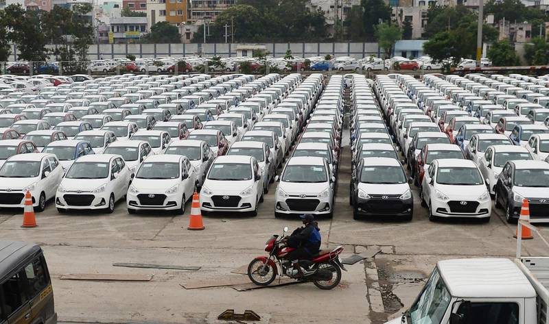 An Indian motorist rides past parked Hyundai vehicles ready for shipment at a port in Chennai on December 1, 2017. (Photo by ARUN SANKAR / AFP)