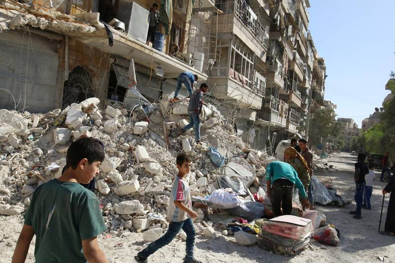 People remove belongings from a damaged site after an air strike Sunday in the rebel-held besieged al-Qaterji neighbourhood of Aleppo, Syria October 17, 2016. REUTERS/Abdalrhman Ismail