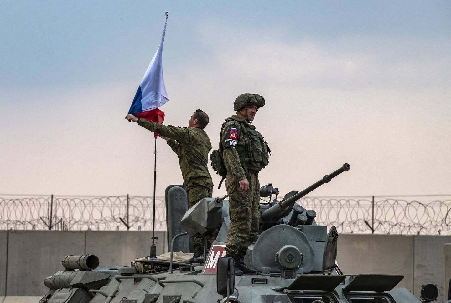 Russian troops on patrol with Turkish forces in the countryside of the town of Darbasiyah in Syria's northeastern Hasakeh province on the border with Turkey, raise a national flag atop an armoured personnel carrier on November 1, 2019. - Turkey started joint patrols with Russia in northern Syria today to verify whether Kurdish forces have withdrawn from a key border zone in compliance with a deal reached between the two governments. (Photo by Delil SOULEIMAN / AFP)