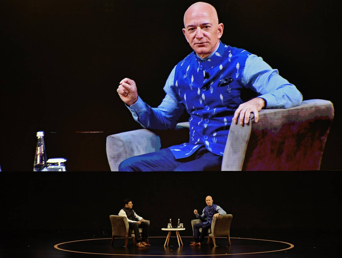 Jeff Bezos, founder and chief executive officer of Amazon.com Inc., right, speaks as Amit Agarwal, head of India, listens during the opening session of Amazon Sambhav event in New Delhi, India, on Wednesday, Jan. 15, 2020. Bezos got a bitter reception during his India visit this week after the country's antitrust regulator initiated a formal investigation hours before his arrival and infuriated small store owners demonstrated in the streets. Photographer: Anindito Mukherjee/Bloomberg