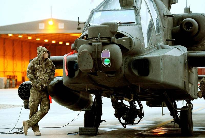 Britain's Prince Harry performs pre-flight checks of his Apache helicopter at Camp Bastion, southern Afghanistan in this photograph taken December 12, 2012, and released January 22, 2013. The Prince, who is serving as a pilot/gunner with 662 Squadron Army Air Corps, is on a posting to Afghanistan that runs from September 2012 to January 2013.  Photograph taken December 12, 2012. Photograph pixelated at source.  REUTERS/John Stillwell/Pool (AFGHANISTAN - Tags: MILITARY CONFLICT ROYALS ENTERTAINMENT POLITICS SOCIETY) *** Local Caption ***  LON706_BRITAIN-HARR_0122_11.JPG