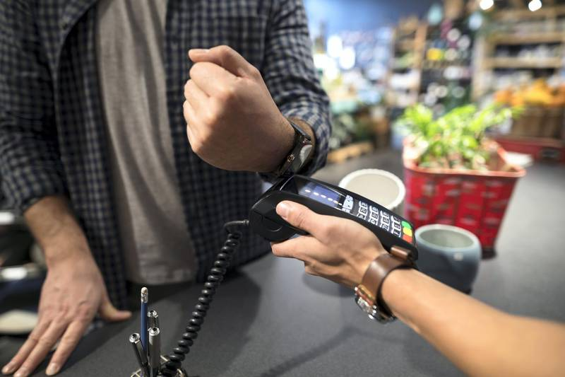 Close up male shopper paying with smart watch contactless payment at plant shop