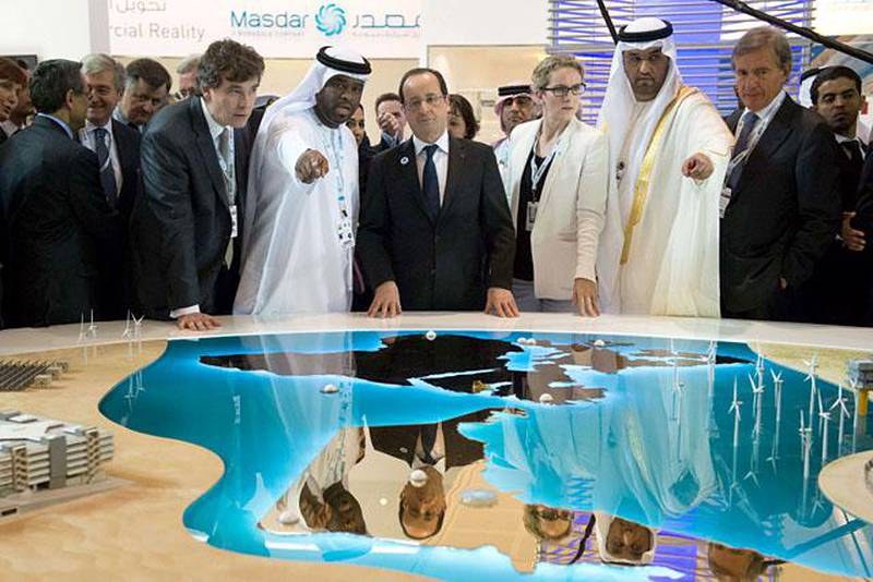 France's President Francois Hollande (C) visits with Sultan Ahmed al-Jaber (2R), chief executive officer of the Abu Dhabi Future Energy Company (MASDAR), French Ecology Minister Delphine Batho (3R), French Minister for Industrial Recovery Arnaud Montebourg (front-L)  during a tour of the company's exhibition at the World Future Energy Summit (WFES) at the Abu Dhabi National Exhibitions Centre (ADNEC) in the Emirati capital on January 15, 2013. AFP PHOTO/BERTRAND LANGOIS