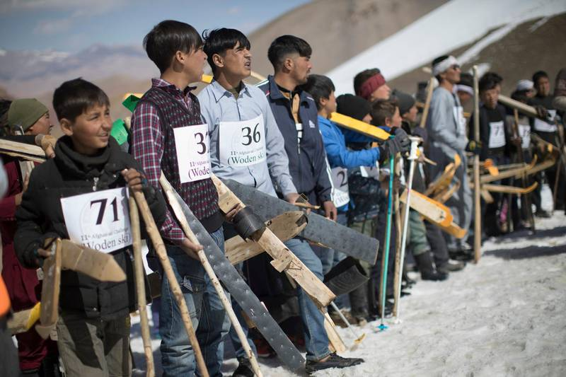 AFGHANISTAN, Bamiyan: 04 March 2021Pictures from the annual Afghan Mountain Challenge - a ski event held in Bamiyan Province, 80 miles west of Kabul. Participants have to run up the mountain via specific checkpoints and then proceed to ski down. Pictured - Local boys prepare for the start of the wooden ski race. Rick Findler for The National