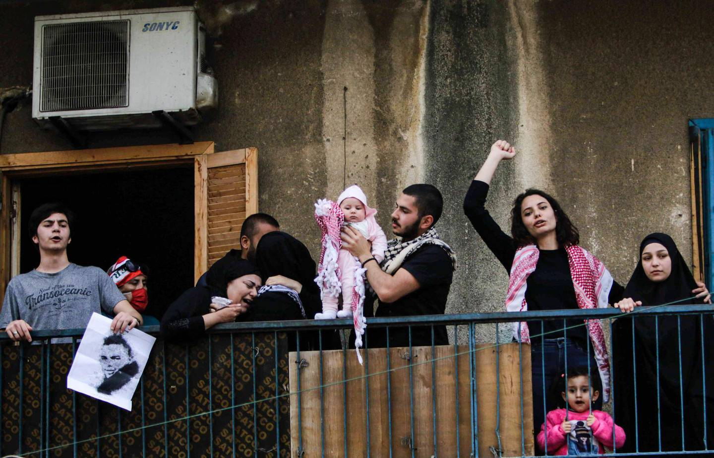 Family members of Lebanese protester Fawwaz al-Samman -- who died after he was shot during riots in late April -- hold up his infant girl and react as they stand in their balcony as protesters coming from acrosss the country gather for a demonstration outside his family home in the northern port city of Tripoli on May 3, 2020.  / AFP / Ibrahim CHALHOUB