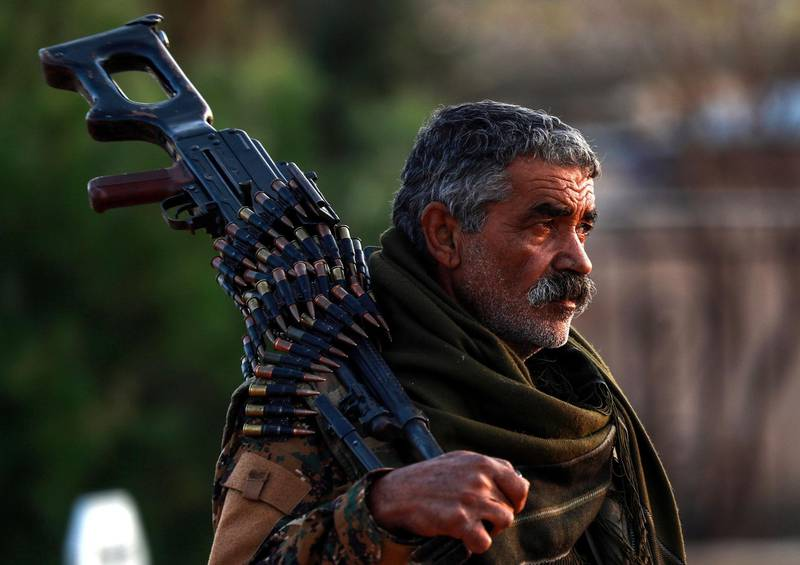 A Syrian Democratic Forces'(SDF) fighter holds a machine gun on his shoulder as he attends the funeral of a slain People's Protection Units (YPG) commander in the northeastern city of Qamishli on December 6, 2018.  / AFP / Delil SOULEIMAN