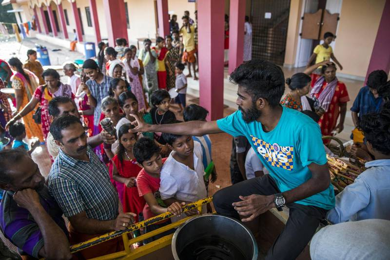 Volunteers serve tea and snacks to flood victims at a relief camp set up at Sree Narayana College Cherthala, affiliated to the University of Kerala, in Alappuzha, Kerala, India, on Thursday, Aug. 23, 2018. India's tourist hub of Kerala is shifting its focus to relief and rehabilitation work to assist millions of people affected by the worst flood in a century as rescue operations wind down. Photographer: Prashanth Vishwanathan/Bloomberg