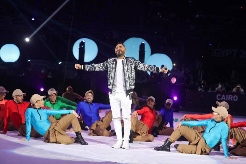 Egyptian singer Tamer Hosni (C) performs with dancers during the opening ceremony prior to the opening match of the 2021 World Men's Handball Championship between Group G teams Egypt and Chile at the Cairo Stadium Sports Hall in the Egyptian capital on January 13, 2021. (Photo by MOHAMED ABD EL GHANY / POOL / AFP)