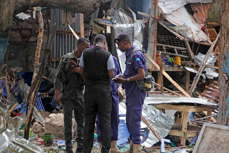 Security forces gather in the remains of destroyed houses after a suicide bomb attack in Mogadishu, Somalia Tuesday, Nov. 17, 2020. Police in Somalia say five people were killed when a suicide bomber detonated an explosives belt near the police academy in the capital, Mogadishu. (AP Photo/Farah Abdi Warsameh)