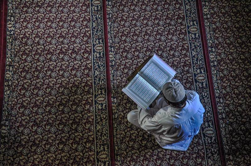 SRINAGAR, J&K, INDIA - 2018/05/31: A Kashmiri man recites the Quran during the ongoing holy month of Ramadan in Srinagar, Indian administered Kashmir. Muslims throughout the world are marking the month of Ramadan, the holiest month in the Islamic calendar during which devotees fast from dawn till dusk. (Photo by Saqib Majeed/SOPA Images/LightRocket via Getty Images)