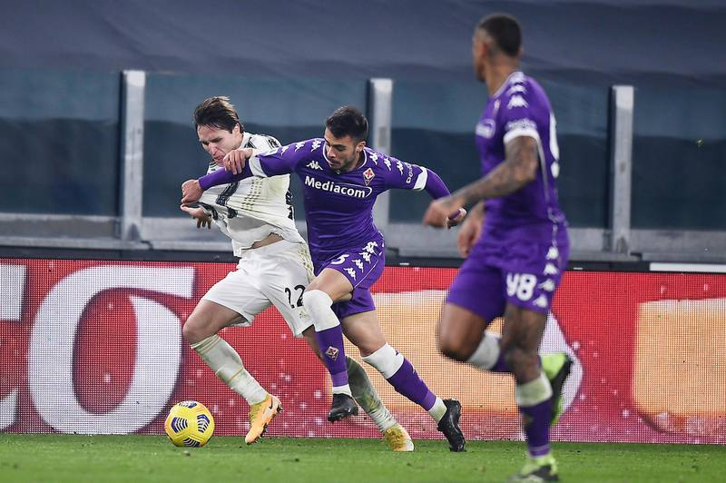 Juventus' Federico Chiesa, left, competes for the ball during the Serie A soccer match between Juventus and Fiorentina, at the Allianz Stadium in Turin, Italy, Tuesday, Dec. 22, 2020. (Fabio Ferrari/LaPresse via AP)