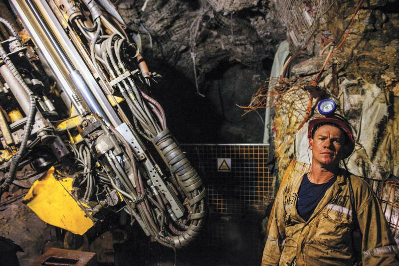 A miner stands beside a drilling machine in an underground tunnel at the South Deep gold mine, operated by Gold Fields Ltd., in Westonaria, South Africa, on Thursday, March 10, 2017. South Deep is the world's largest gold deposit after Grasberg in Indonesia, makes up 60 percent of the company's reserves and the miner says it's capable of producing for 70 years. Photographer: Waldo Swiegers/Bloomberg