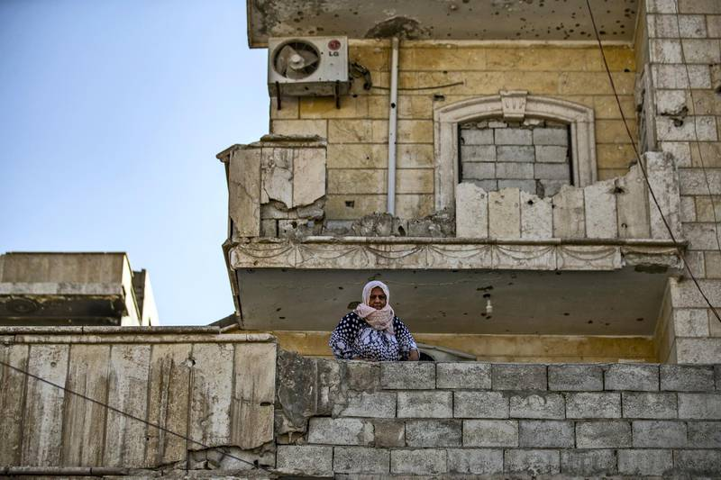 A woman stands in front of a bullet riddled facade in the northern Syrian city of Raqa, the former Syrian capital of the Islamic State (IS) group, on August 21, 2019. - The Kurdish-led Syrian Democratic Forces overran Raqa in 2017, after years of what residents described as IS's brutal rule, which included public beheading and crucifixions. (Photo by Delil SOULEIMAN / AFP)